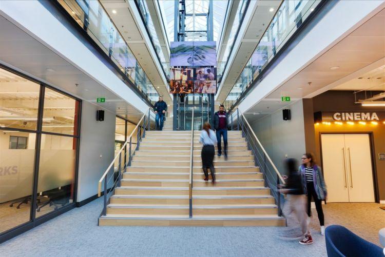 Staff walking up wooden stairs in modern office design