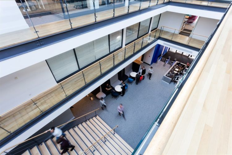 Looking down into office reception in a modern office with light wooden floorboards