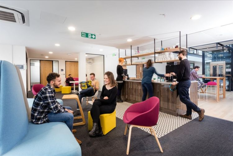 Staff talking in a breakout area with colourful furniture