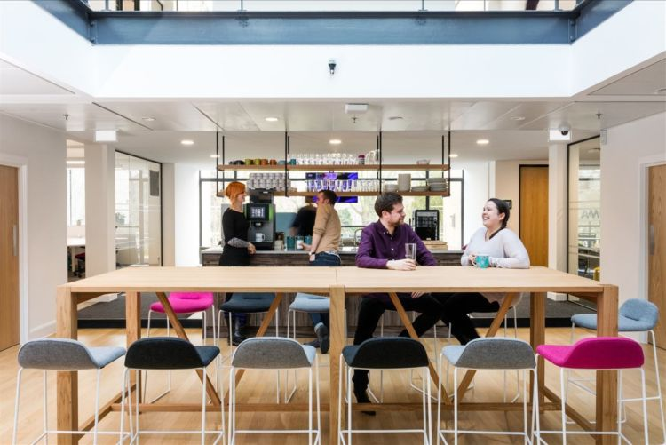 Coffee and break area in a modern office design with coloured bar stools