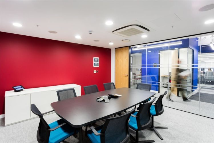 Red wall in an open plan modern office meeting room