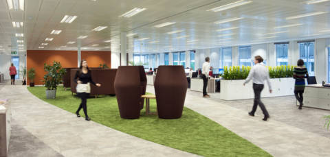 Green carpet and coffee pod seating in the middle of an open plan office space