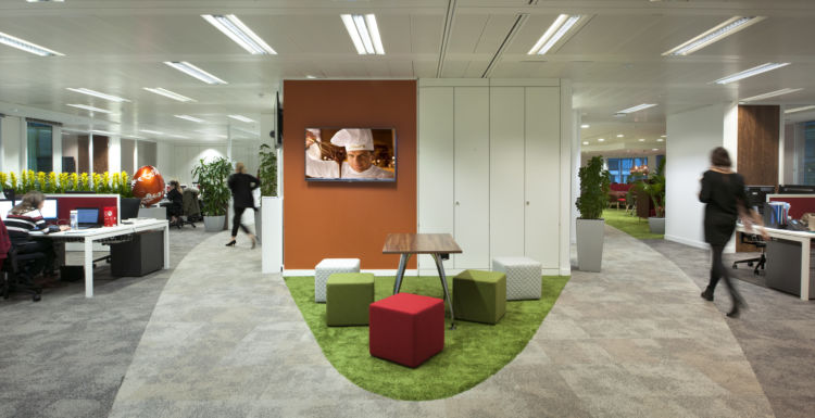 Colourful ottomans and green carpet in impromptu meeting area