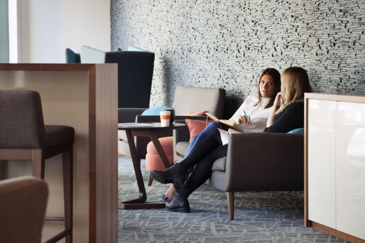 Two colleagues meeting in a modern breakout area