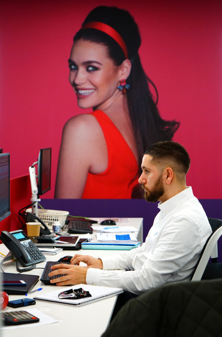 Man working in colourful workstation area with photo prints