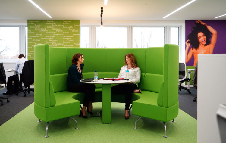 Colleagues having meeting in a green pod chair in a modern office