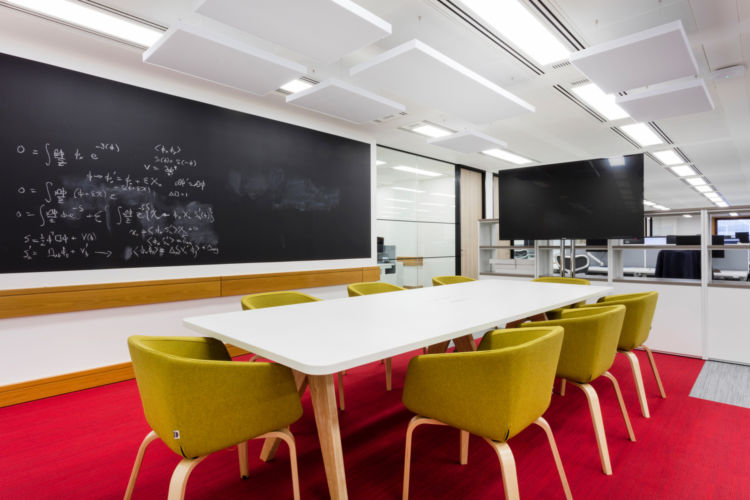 Desks surrounded by red flooring and a chalkboard provide a modern twist to this London office fit out