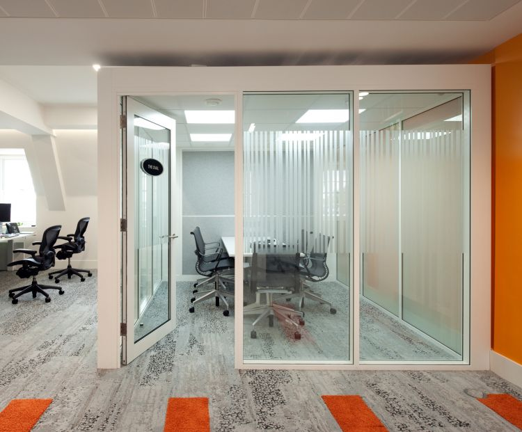 Glass meeting room with orange walls in modern office design for eBay
