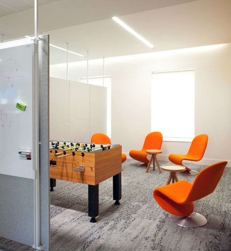 Orange chairs and foosball table in funky staff breakout area in designer office fit out