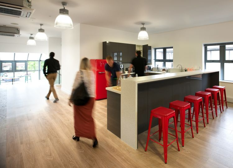 Staff kitchen with red bar stools in modern open plan office design