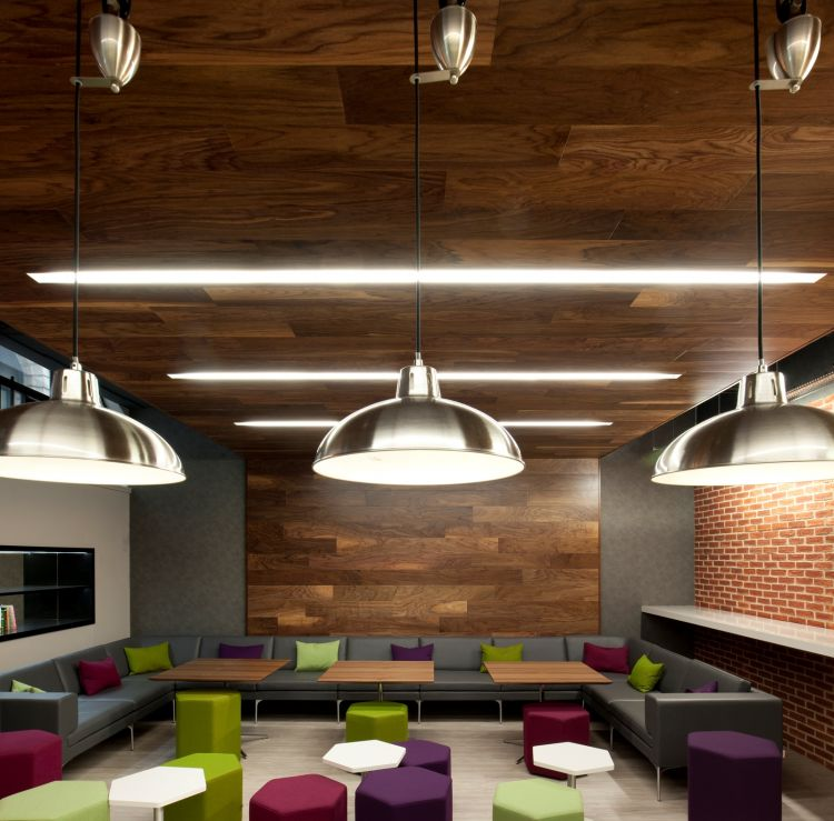 Wooden ceiling panels and exposed brick walls provide a modern finish