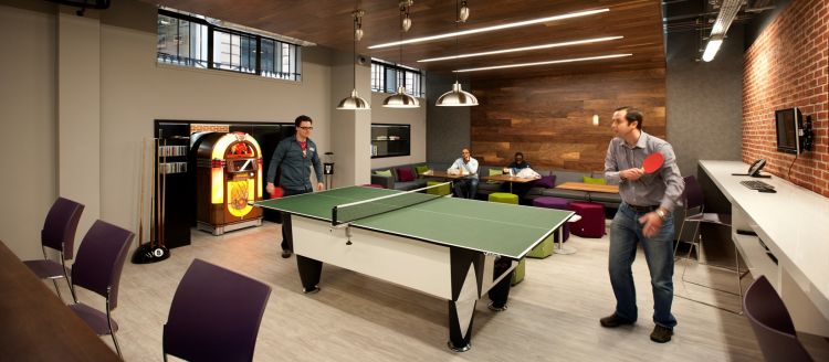 Staff playing table tennis in funky office breakout area with jukebox and wooden walls