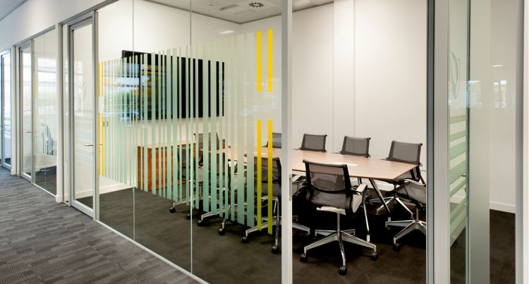 Meeting room with glass walls and yellow barcode-style detailing