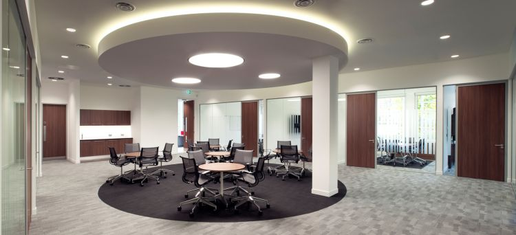 Collaborative desks in open plan office fit out with suspended circular ceiling and mood lighting