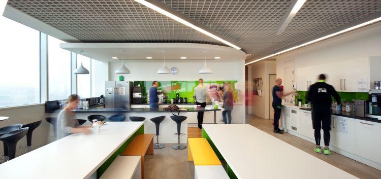 Busy staff kitchen with coloured splashbacks in designer office
