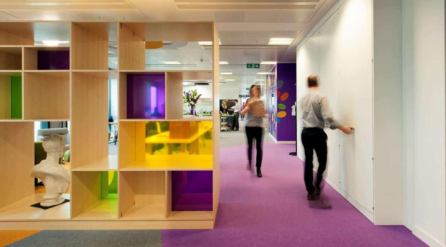 Coloured cubicles provide storage space and break up this open plan office fit out