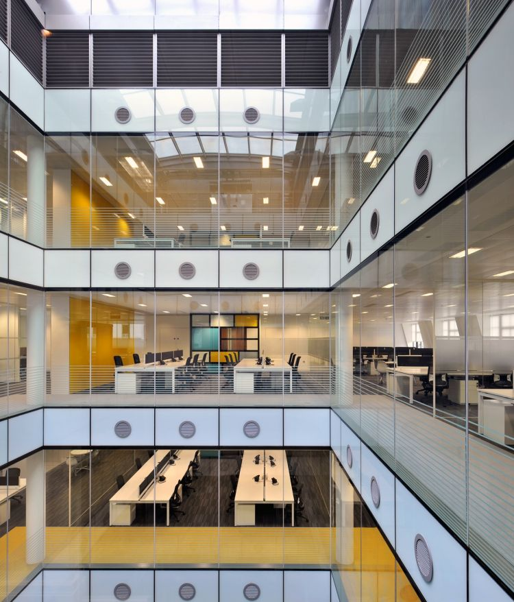 View from central atrium into funky and colourful offices with workstations