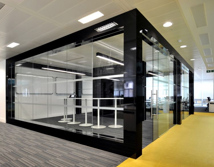 Large private standing meeting room with whiteboards, farmed with black paneling