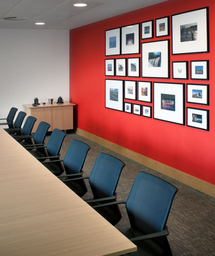 Modern boardroom with picture frames on a red wall