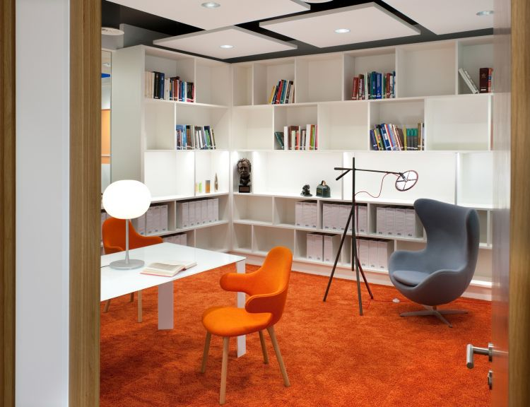 Library style room with orange chairs and carpet in funky designer office