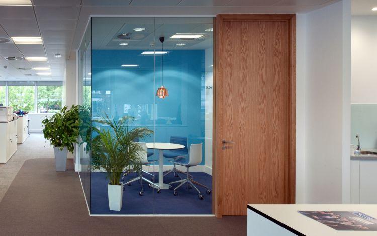 Blue themed corner office with a solid oak door inside modern office