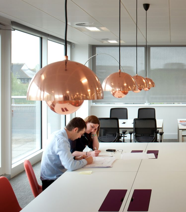 Brass pendant lights and a colleagues reading a document in open plan office