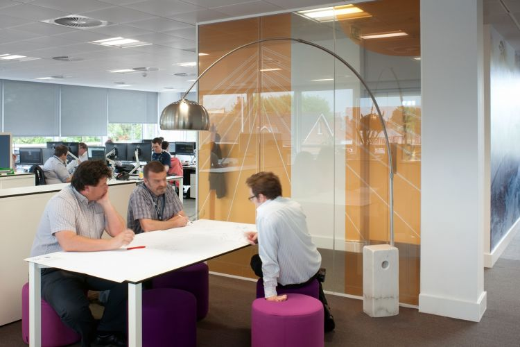 Pendant light handing over three colleagues working in a modern office fit out