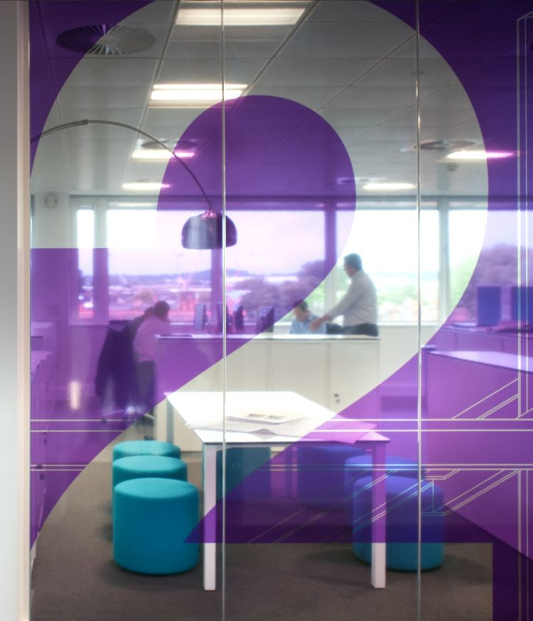 Large number 2 on purple glass looking over modern office