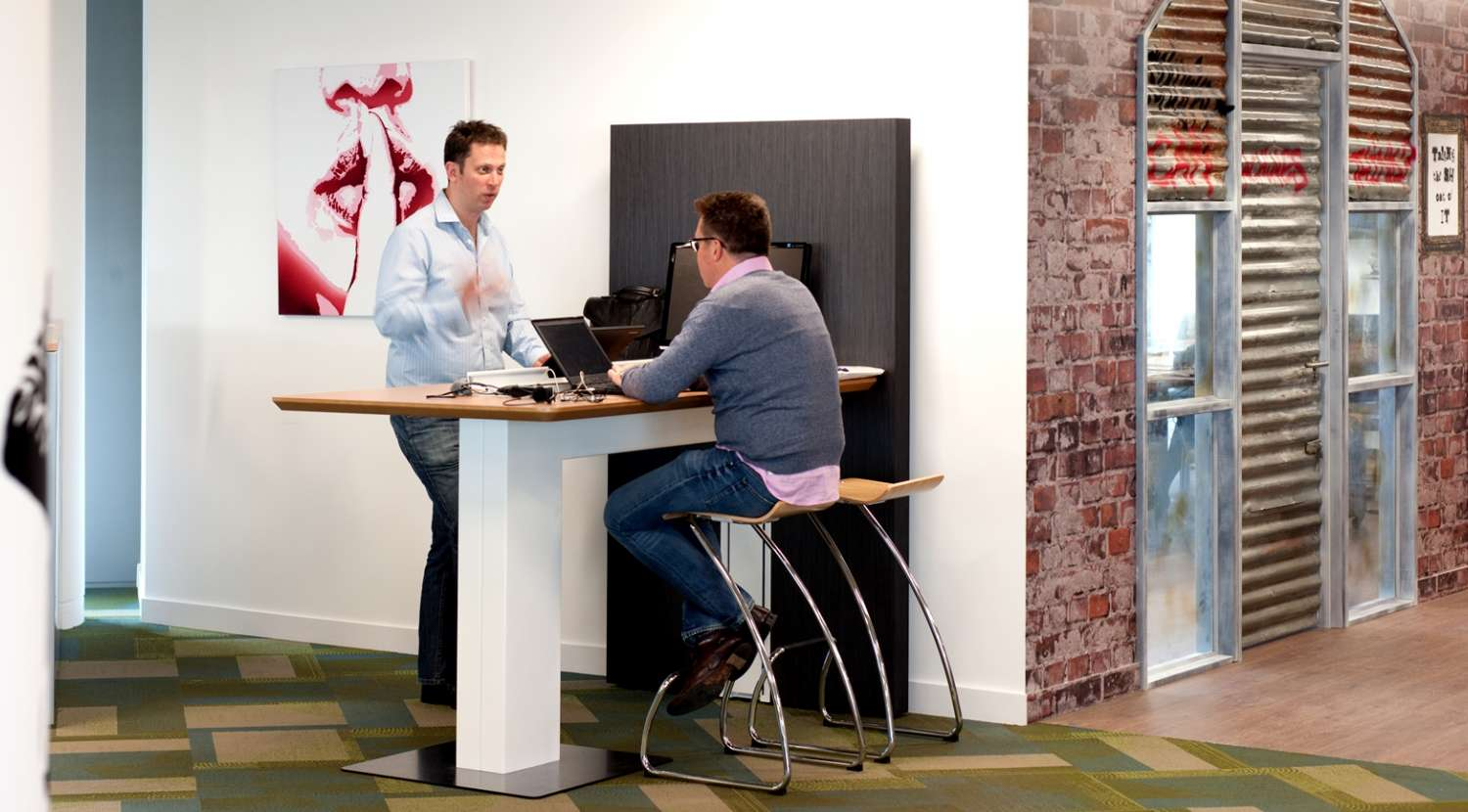 Staff at a standing meeting area in the Splunk office fit out