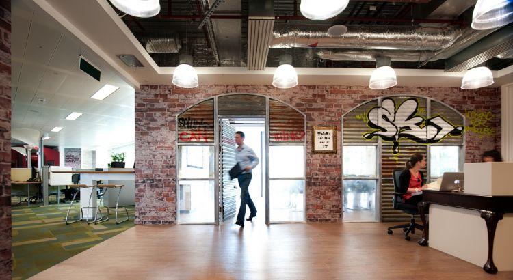 Staff walking through mock railway arches into the Splunk office boardroom