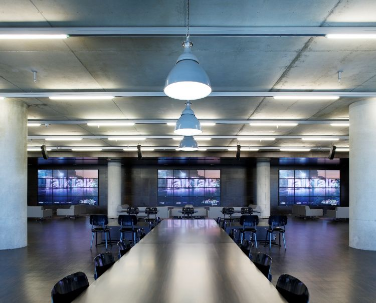 Exposed concrete ceiling and walls with TVs in modern office fit out