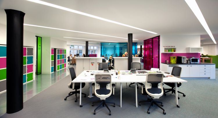 White workstations with bright coloured walls and storage cubicles in this funky office design