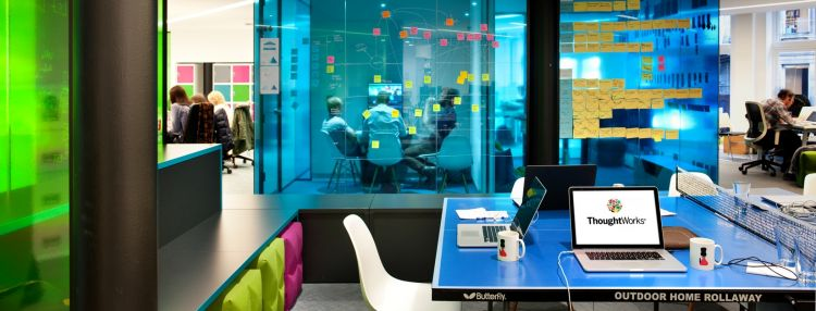 Bright coloured office design with glass divider pannels covered in post-it notes