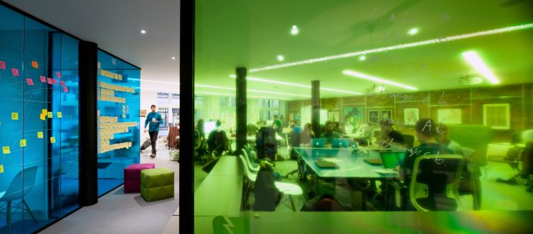 Open plan startup style office with coloured glass panels and post-it notes on the walls