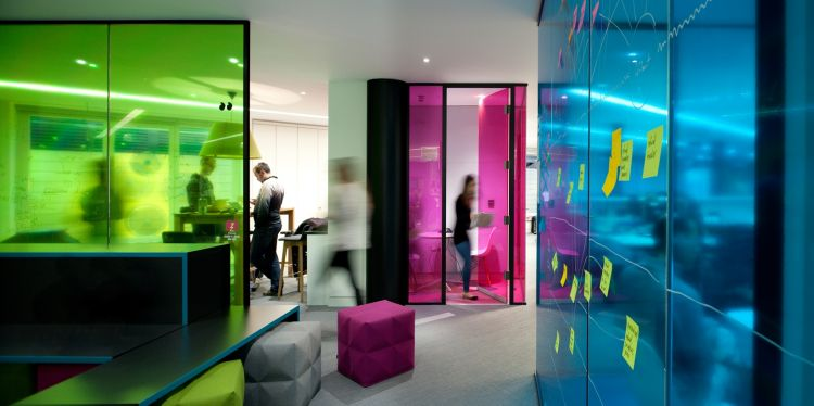 Bright blue and green opaque panels breakup this open plan office space