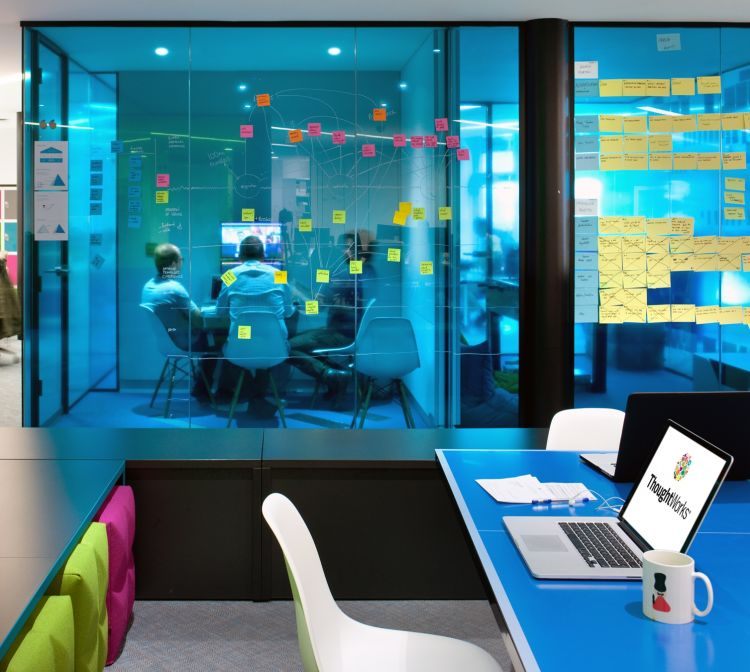 Staff gathering in a blue themed meeting room / London Office Design